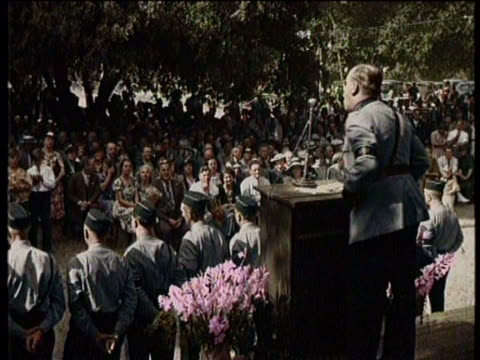 Newsreel / No audio / Military figure addressing a crowd outside while a line of military men stand before the stage /