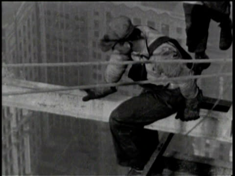 newsreel / no audio / one worker scoots out onto a beam with no harness / a camera man films him / arial view of men on beams with new york city in... - chrysler building stock videos & royalty-free footage