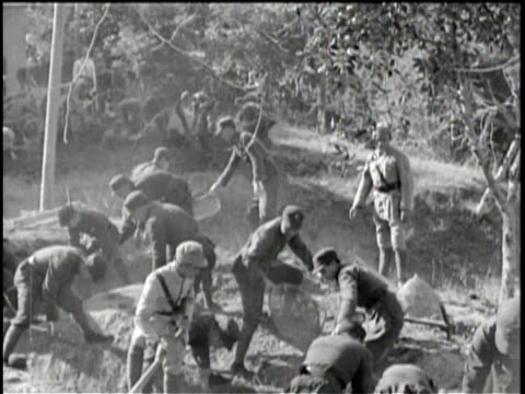 newsreel / no audio / pathe news / china's youth train for military service / soldiers running two by two with shovels / soldiers digging trench... - pacific war video stock e b–roll