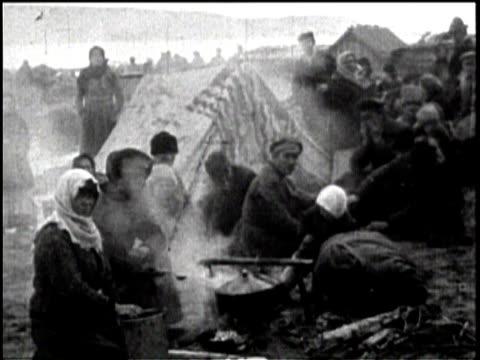 vídeos de stock, filmes e b-roll de newsreel / no audio / pathe news / footage of russian civilians under the soviet five year plan / pan of russian civilians standing outside of an... - indo em direção