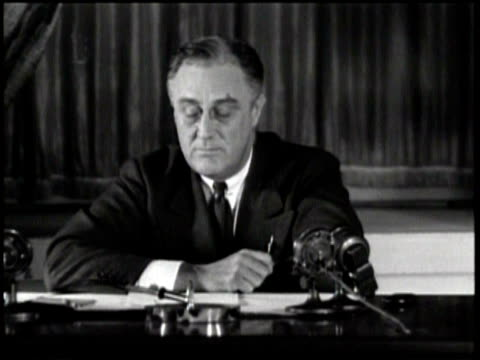 vídeos y material grabado en eventos de stock de newsreel / no audio / pathe news / title card reads roosevelt reports to the nation / franklin d roosevelt sits at desk in front of microphones... - franklin roosevelt