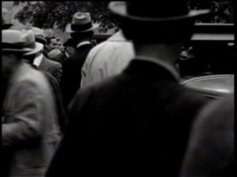 newsreel / no audio / people come out of a large building with pillars and a large staircase / a man is escorted out of an old modelt as cameras... - model t stock videos and b-roll footage