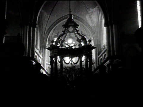 newsreel / no audio / people standing up during a religious service / religious figures standing at the front of the sanctuary / a line of men... - religious service stock videos and b-roll footage