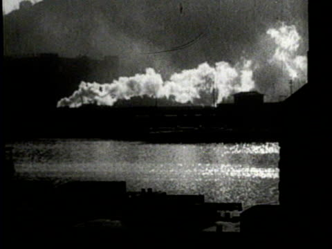 newsreel / no audio / smoke billows from multiple smoke stacks at night near the water / - smoke stack stock videos & royalty-free footage