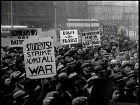 newsreel / no audio / title card reads pathe news / people protest the war in new york in 1940 / old cars line the road as people walk with an... - report produced segment stock videos & royalty-free footage
