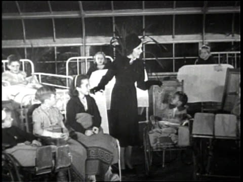 newsreel / no audio / woman dressed in black in room with several children in wheelchairs / woman bending over and pinching cheek of small child in... - cheek to cheek stock videos & royalty-free footage