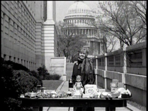 newsreel / no audio / woman standing behind a table with various objects / capitol building in the background / woman addressing the camera directly... - made in the usa kort fras bildbanksvideor och videomaterial från bakom kulisserna