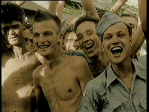 newsreel / no audio / world war 2 / allied prisoners of war on a coast holding the british union jack the american and french flags / shirtless... - ほっそりした点の映像素材/bロール
