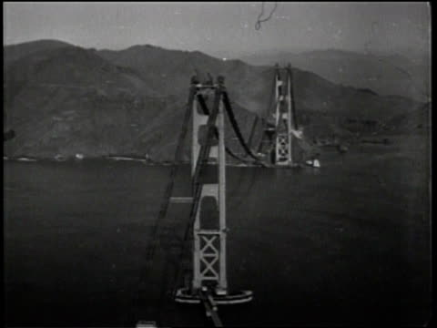 newsreel / title card reads: news flashes! / no audio / blimp flying over golden gate bridge in san francisco, california / pilots in blimp turning... - golden gate bridge stock videos & royalty-free footage