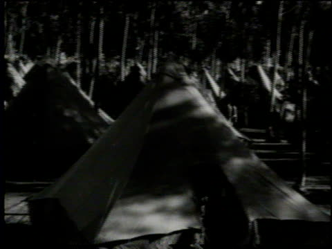 stockvideo's en b-roll-footage met newsreel / victims left homeless by earthquake sleep in army tents in the parks of long beach / wooded park filled with tents / woman with a baby... - 1933