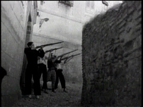 newsreel / warfare in the streets / men with rifles shoot at each other in the streets of spain / - 1938 stock-videos und b-roll-filmmaterial