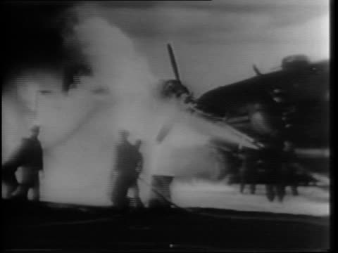 vídeos de stock e filmes b-roll de newsreel / wide shot of a sequence of vehicles driving toward bomber with equipment / interior shot of bomb bay doors opening on bomber with truck... - 1944