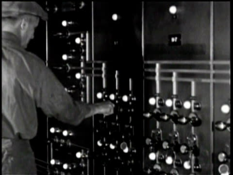 newsreel / workers build two-mile tunnel under hudson river in new york / interior of tunnel control room / worker adjusts knob on wall panel off... - hand of cards stock videos & royalty-free footage