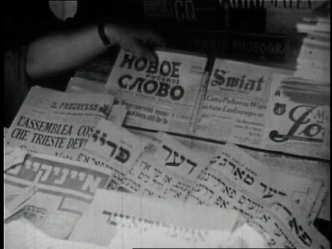 1946 montage newstand with newspapers of different national origins, man buying paper / lower east side, new york city, new york, united states - einwanderer stock-videos und b-roll-filmmaterial