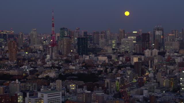 vídeos de stock, filmes e b-roll de arquitectura da cidade nova/tokyo-lua que levanta-se acima dos arranha-céus - meia noite