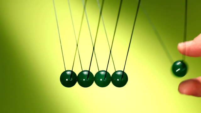 Newton's cradle of green balls