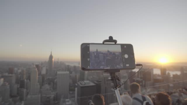 vídeos de stock, filmes e b-roll de newyork_15_4k_manhatten_topoftherocks_topshot_people_mobile - ponto de observação