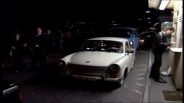 nght shot of people at berlin wall crossing - 1980 1989 stock-videos und b-roll-filmmaterial
