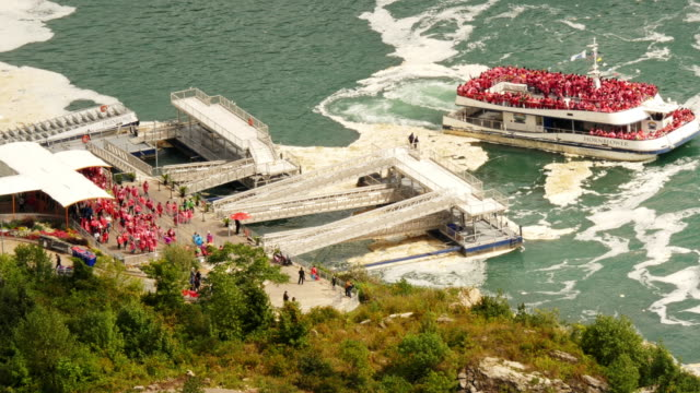 niagara cruise boat hornblower with passengers in red ponchos  departing from pier. view from above. - spoonfilm stock-videos und b-roll-filmmaterial