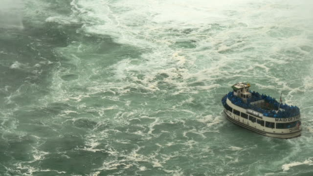 niagara cruise boat maid of the mist  fighting current and turning around in the horseshoe falls – aerial view, narrow shot - spoonfilm stock-videos und b-roll-filmmaterial