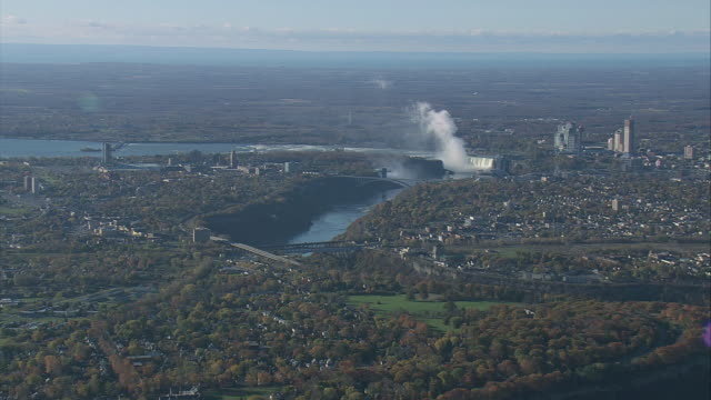 AERIAL Niagara Falls, with vapor boiling up, the Niagara River, and urban sprawl on both banks / Niagara Falls, New York, United States