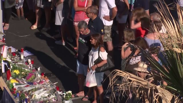 stockvideo's en b-roll-footage met mourners pay tribute along promenade as six people in custody various of people gathered around flowers and other tributes laid in memory of the... - rouwende