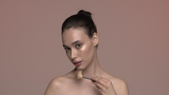良い肌を持つ素敵な女の子は、ブラシでメイクアップを適用します。 - 絵画モデル点の映像素材/bロール
