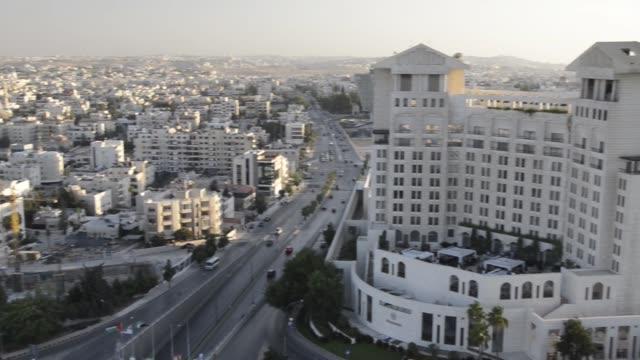 nice pan of jordan reveals major road and sheraton amman al nabil hotel and traffic - major road stock-videos und b-roll-filmmaterial