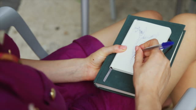 nice woman drawing on a sketchbook outdoor at bar - sketch pad stock videos and b-roll footage