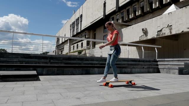 vídeos de stock, filmes e b-roll de bela jovem andando de skate ao ar livre, movimento lento - camiseta
