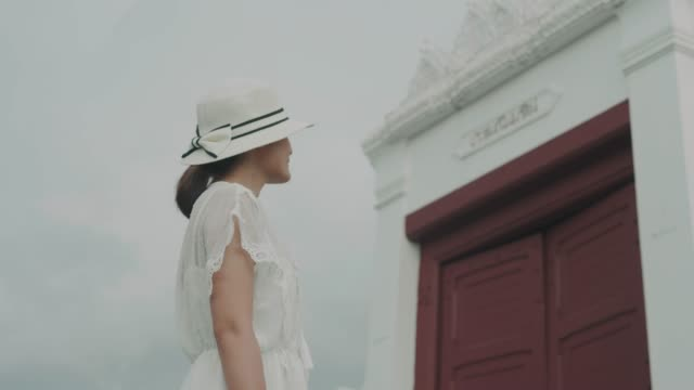 Niche beautiful woman wearing white hat and dress looking to the door of temple in Bangkok for travel