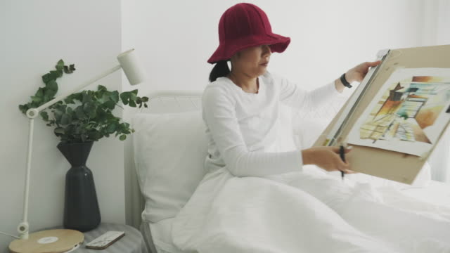 niche woman interior artist wear red hat is drawing and sketching for her leisure activity at her white bedroom - hot desking stock videos & royalty-free footage