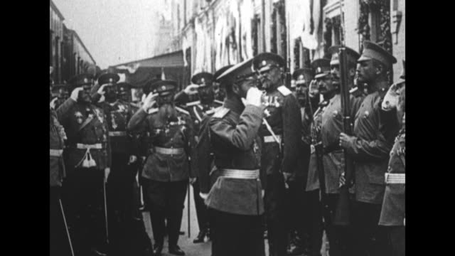 Nicholas II inspecting military officers / Nicholas with officers and priest walking across field / Nicholas with officers walking along front of...