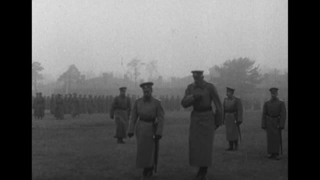 Nicholas II inspects troops walks with a priest and he and very tall cousin Grand Duke Nicholas Nikolaevich walk with others on a misty parade ground...