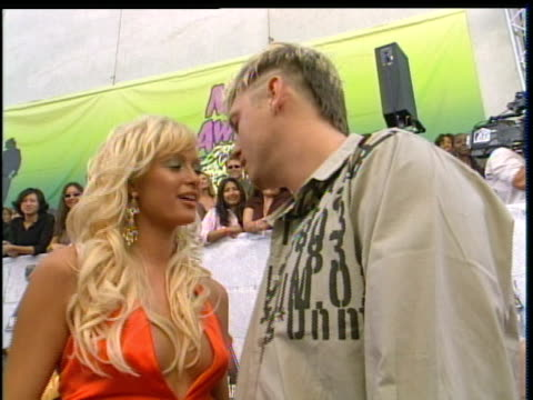 stockvideo's en b-roll-footage met nick carter and paris hilton whispering into each other's ear. nick carter and paris hilton showing paris hilton's dress off at the 2004 mtv movie... - 2004