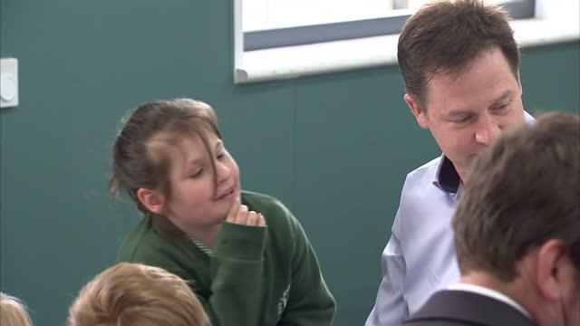 nick clegg & miriam durantez visit ivy lane school in chippenham. shows interior shots nick clegg talking with schoolchildren at dining table in... - チッペナム点の映像素材/bロール