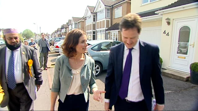 nick clegg says 'snoopers' charter' will not become law while liberal democrats are in government; watford: ext clegg along to put leaflet into door... - seguire attività che richiede movimento video stock e b–roll