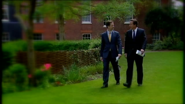 nick clegg threatens veto on nhs reforms lib london downing street david cameron mp and clegg along through garden on first day of coalition... - 1日目点の映像素材/bロール