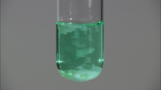 Nickel (II) hydroxide precipitate, formed as sodium hydroxide is dripped into nickel (II) chloride