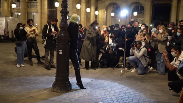 vidéos et rushes de nicky doll wears a black jacket, a large belt, black leather pants, black leather high heeled pointy boots, poses in front of photographers, outside... - éclairage au flash