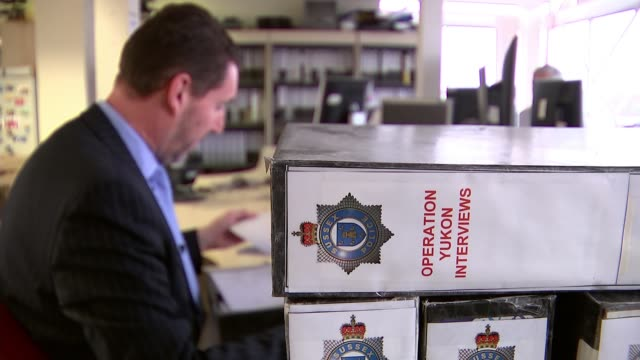Russell Bishop found guilty ENGLAND Sussex EXT Police officer working at desk with folder 'Operation Yukon Interviews' in foreground Police officer...