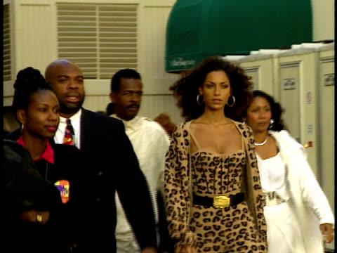Nicole Mitchell Murphy wears a leopard design outfit walks along red carpet