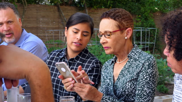 ms niece helping aunt use smartphone during family dinner party - sharing stock videos & royalty-free footage