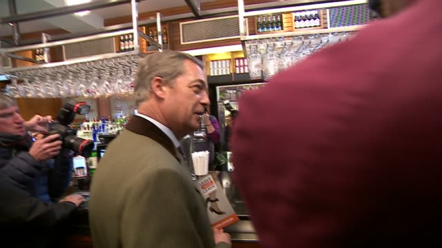Nigel Farage ordering a pint of ale in a pub in Bolton
