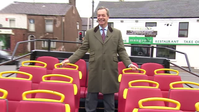 Nigel Farage posing atop an opentop double decker bus as it drives through Bolton