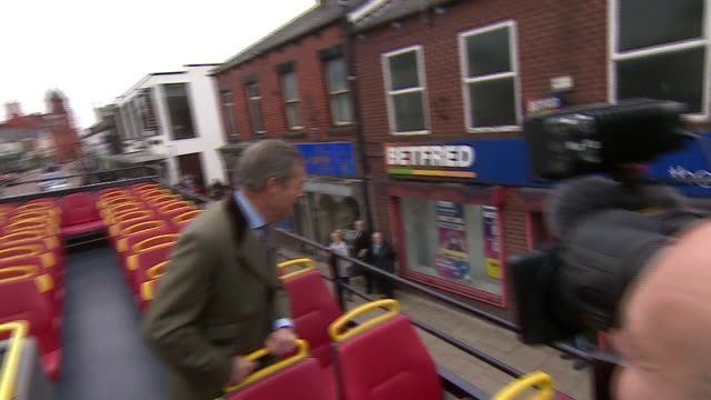 Nigel Farage waving and speaking to supporters from atop an open top double decker bus as it drives through Bolton