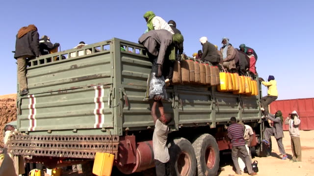 / Niger Agadez migrants boarding a truck for the journey across the desert / hanging outside the truck are yellow canisters for water