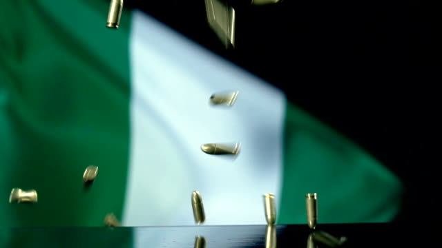 nigerian flag behind bullets falling in slow motion - nigerian flag stock videos & royalty-free footage
