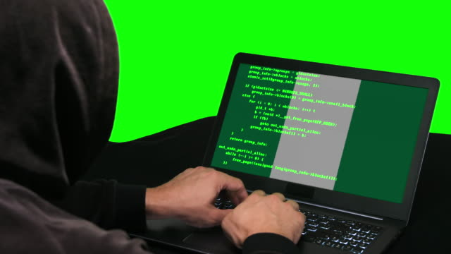 nigerian hacker typing code hacking on his laptop with nigerian flag on it green screen background - nigerian flag stock videos & royalty-free footage