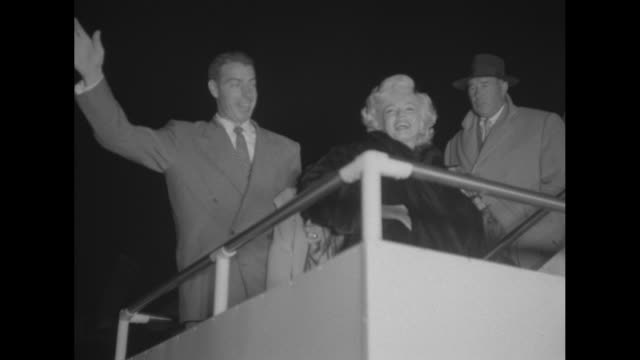 stockvideo's en b-roll-footage met actress marilyn monroe wearing a dark fur coat deplanes from pan american airlines flight as man stands near door her husband baseball star joe... - marilyn monroe
